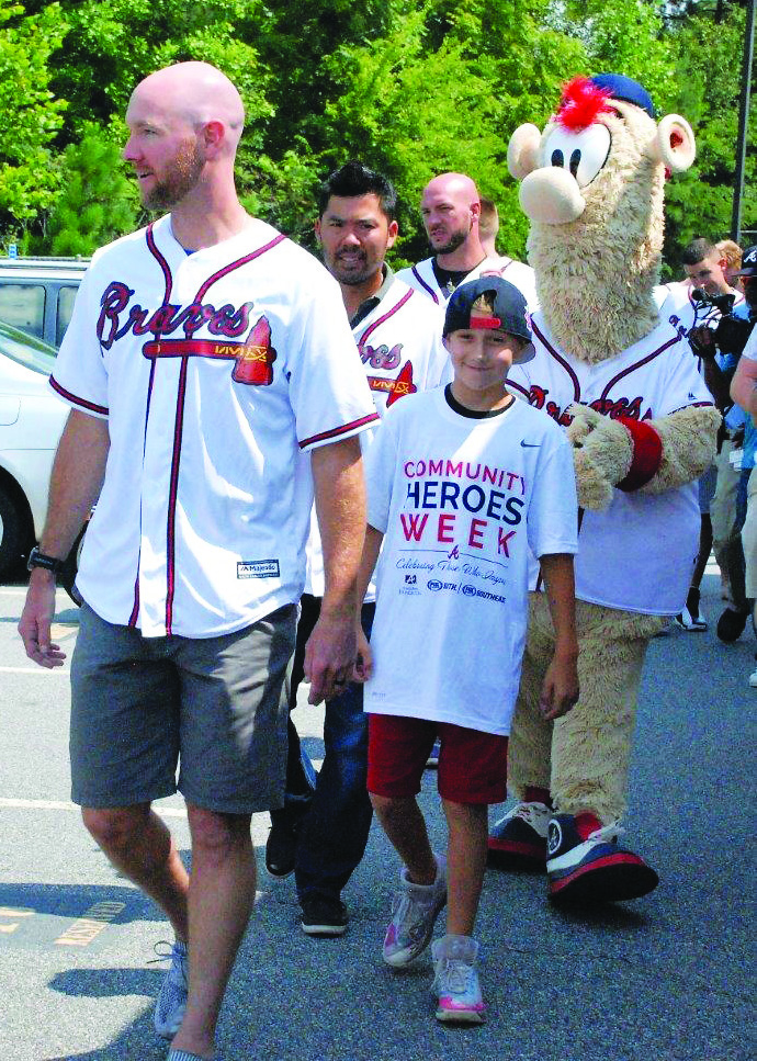 Braves' Community Hero Award winner Mill Creek Middle School seventh-grader Bronco Reece walks with Braves players Jonny Venters and Kurt Suzuki to the field for a game of wiffle ball.