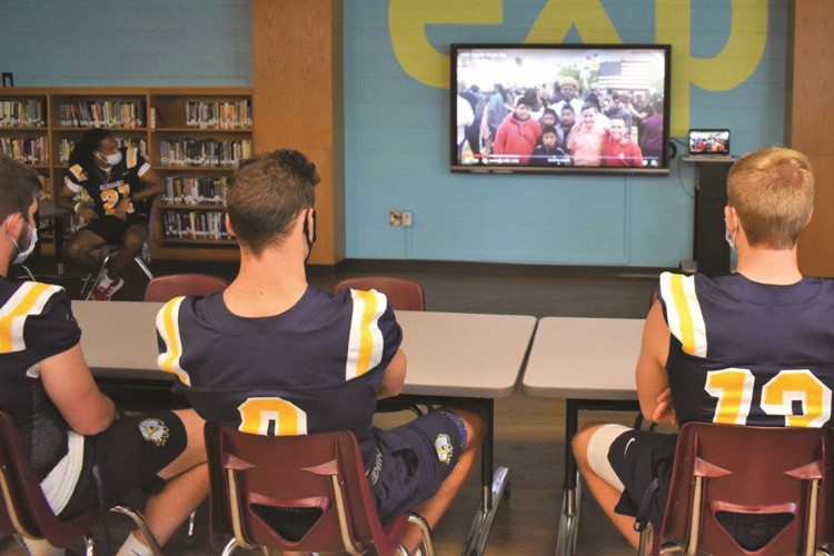 Reinhardt University Football Team players watch a video featuring R.M. Moore ES STEM Academy students thanking them for volunteering as their mentors through the team's partnership with the school.