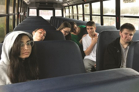 Students, playing the roles of injured Cherokee High School students, wait on a bus for their classmates as they are evacuated from the school during the multi-agency emergency response drill on Thursday.