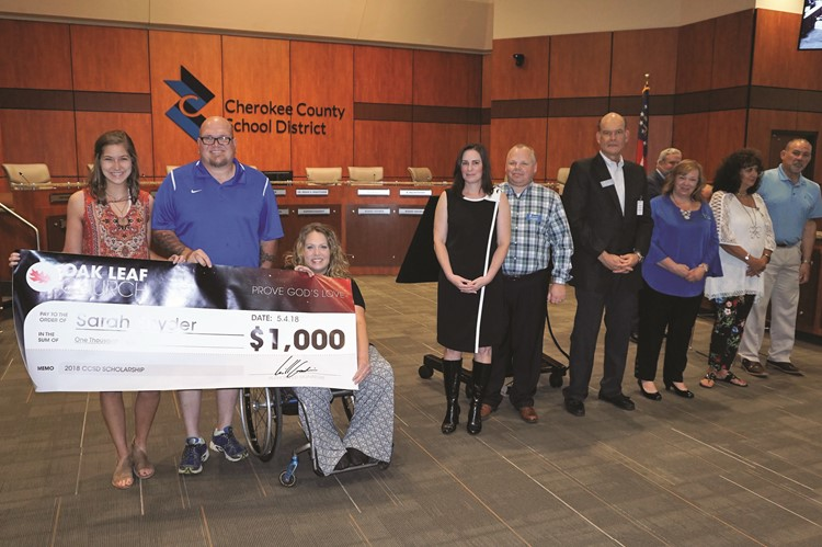 Oak Leaf Church Youth Coordinator Jamie Goodwin, third from left, presents a $1,000 college scholarship to Cherokee HS senior Sarah Snyder at a Cherokee County School Board Meeting.