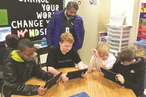 Oak Grove ES Fine Arts Academy fifth-graders show off their coding skills for Cherokee County School District Chief Information Officer Bobby Blount; from left to right: Demetrius Jones, Brady Colton, Christopher Zaski, and Jake Wright