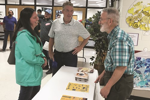 Kendall Jones of MUST Ministries, right, talks with guests at the event about the nonprofit organization's services and volunteer opportunities.