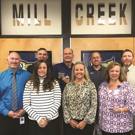 School Board members pose with Mill Creek MS leaders for a photo as part of their visit to the school.  From left to right, front row: Principal Matthew May, Assistant Principals Stacey Krutz and Leigh Gutierez, School Board Chair Kyla Cromer; back row: Deputy Superintendent Trey Olson, School Board members Mike Chapman and John Harmon, Assistant Principal Paul Jones.