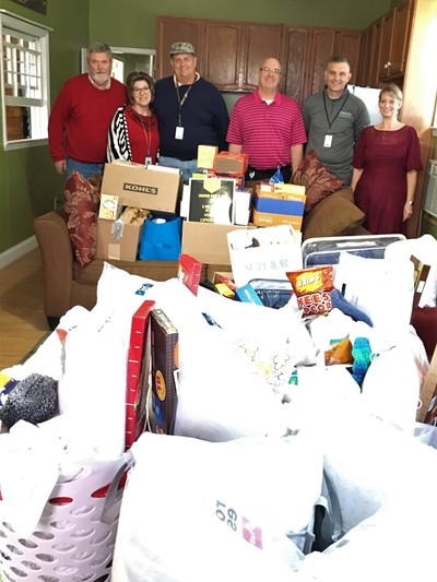 group of employees pose with big pile of donations