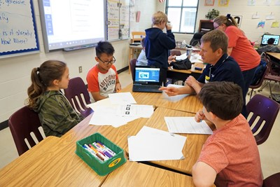 students work with researcher on engineering problem